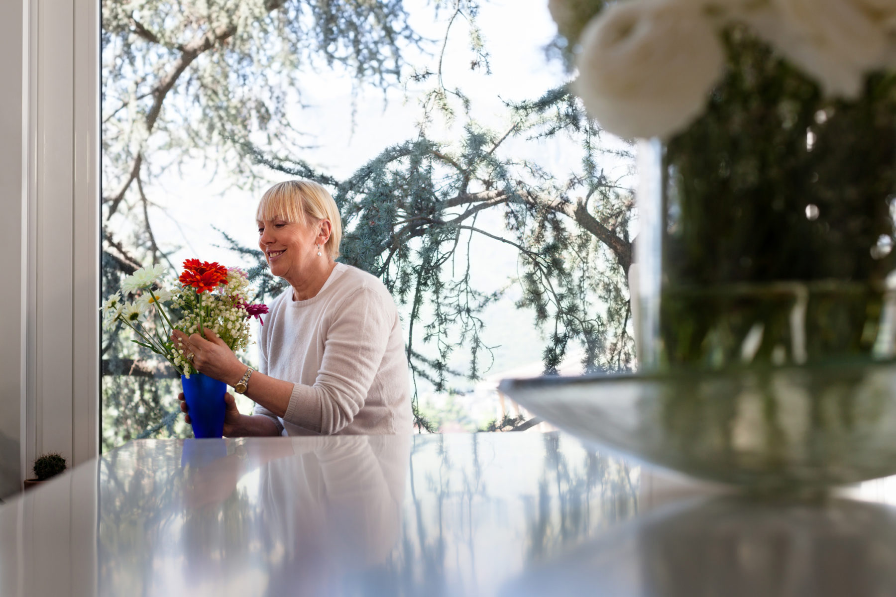 Woman Enjoying flowers in the home