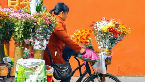 Lady riding the bike with flowers in the basket